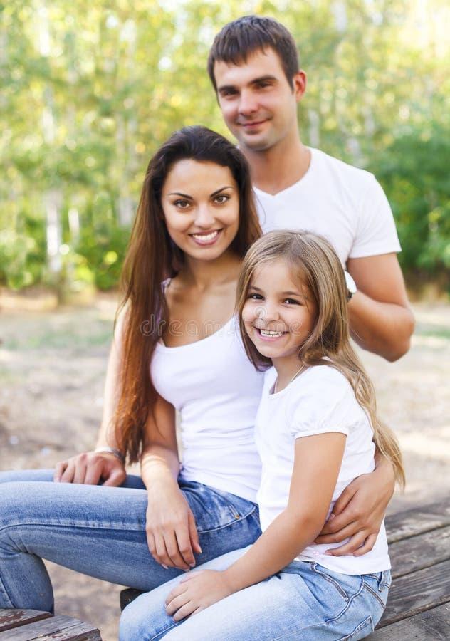 Gelukkige moeder, vader en hun dochter in het park stock afbeeldingen