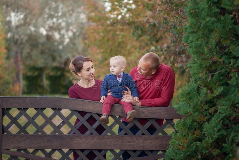 Gelukkige moeder, vader en zoon in het park Geluk in gezinsleven in de zomerdag stock foto