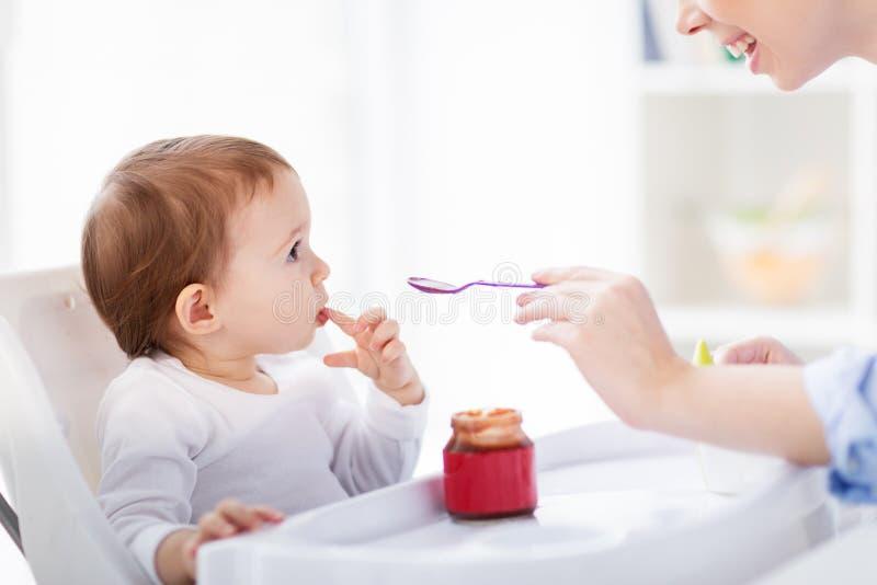 Gelukkige moeder voedende baby met puree thuis royalty-vrije stock afbeeldingen