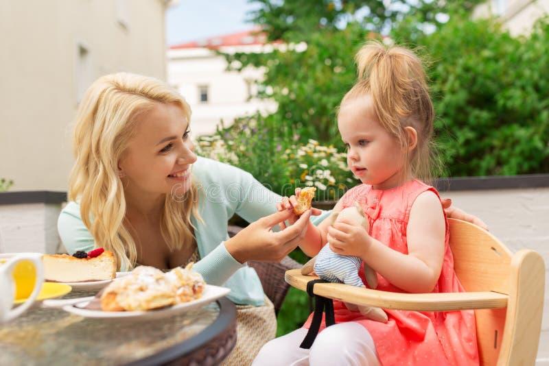 Gelukkige moeder voedende dochter met cake bij koffie stock foto