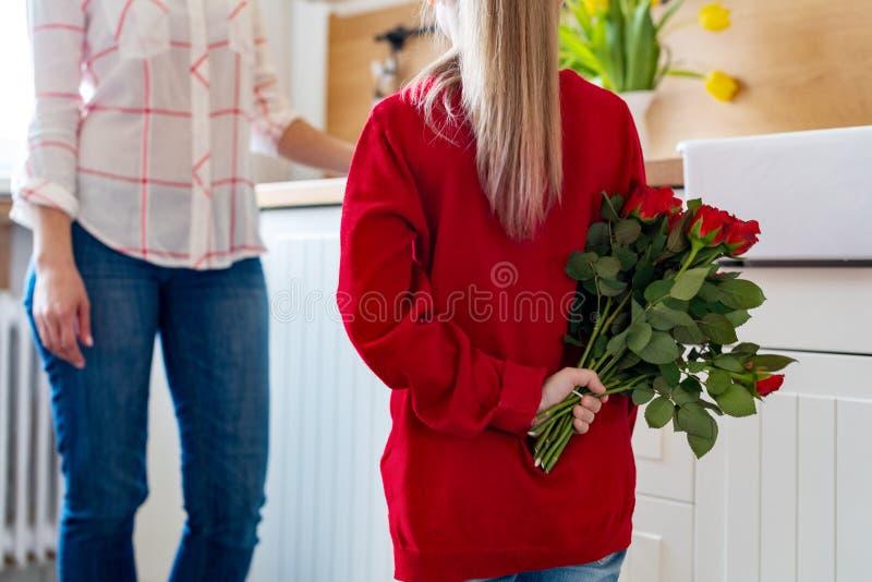 Gelukkige Moederdag of Verjaardagsachtergrond Aanbiddelijk jong meisje die haar mamma met boeket van rode rozen verrassen Familie stock foto's