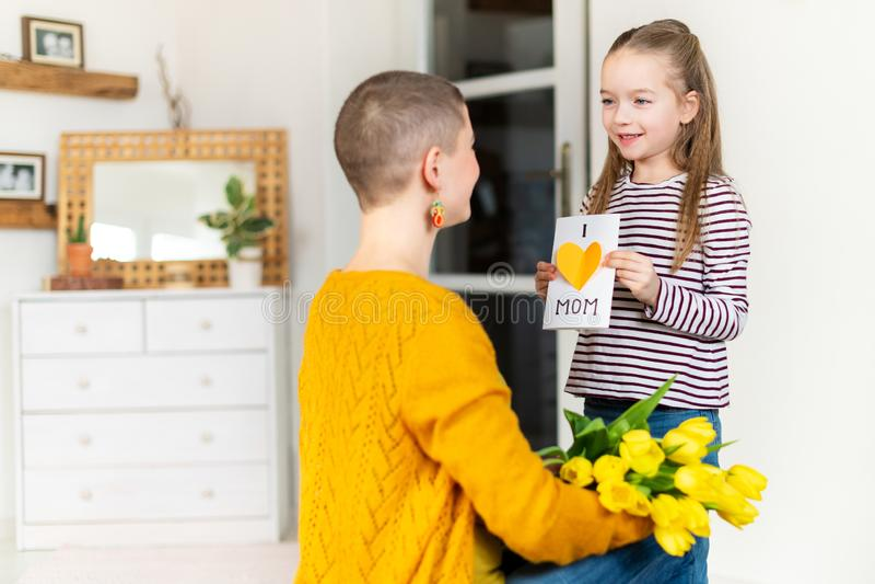 Gelukkige Moederdag of Verjaardagsachtergrond Aanbiddelijk jong meisje die haar mamma met eigengemaakte groetkaart verrassen Fami royalty-vrije stock foto's