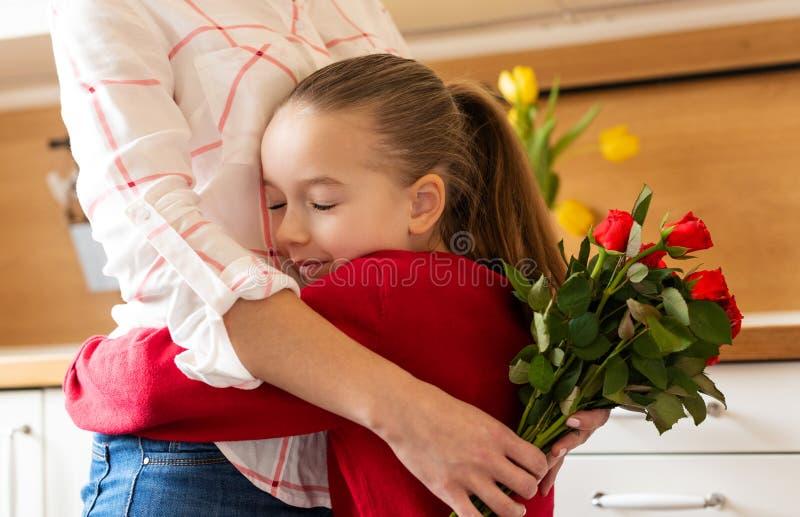 Gelukkige Moederdag of Verjaardagsachtergrond Aanbiddelijk jong meisje die haar mamma na het verrassen van haar met boeket van ro royalty-vrije stock fotografie