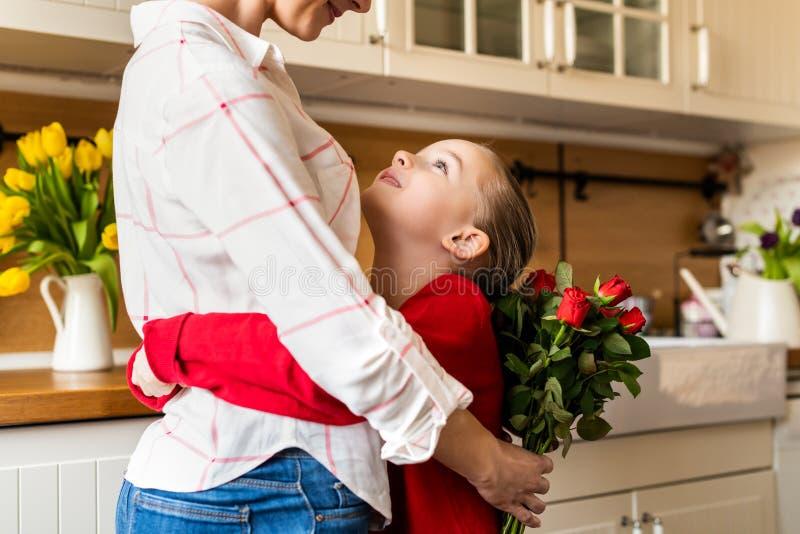Gelukkige Moederdag of Verjaardagsachtergrond Aanbiddelijk jong meisje die haar mamma na het verrassen van haar met boeket van ro stock afbeelding