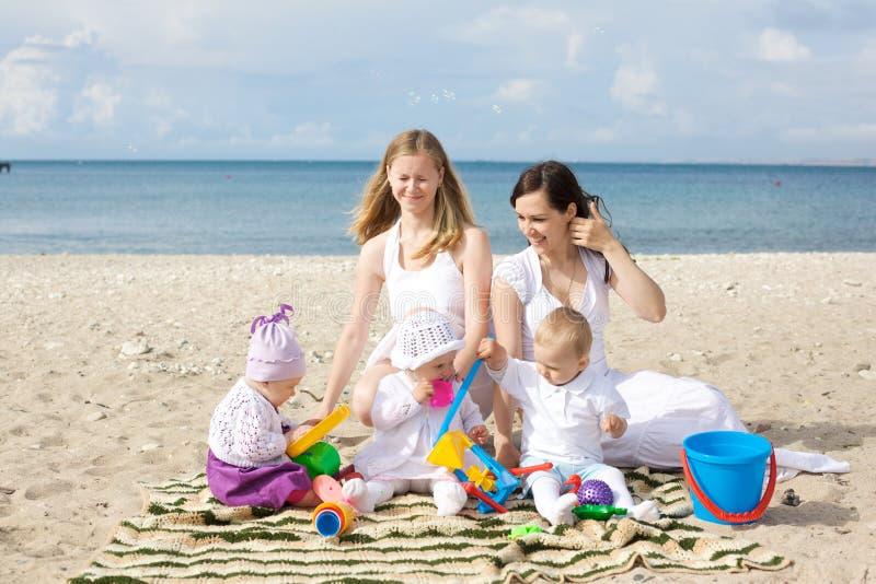 Gelukkige moeders met kinderen bij het strand royalty-vrije stock afbeeldingen