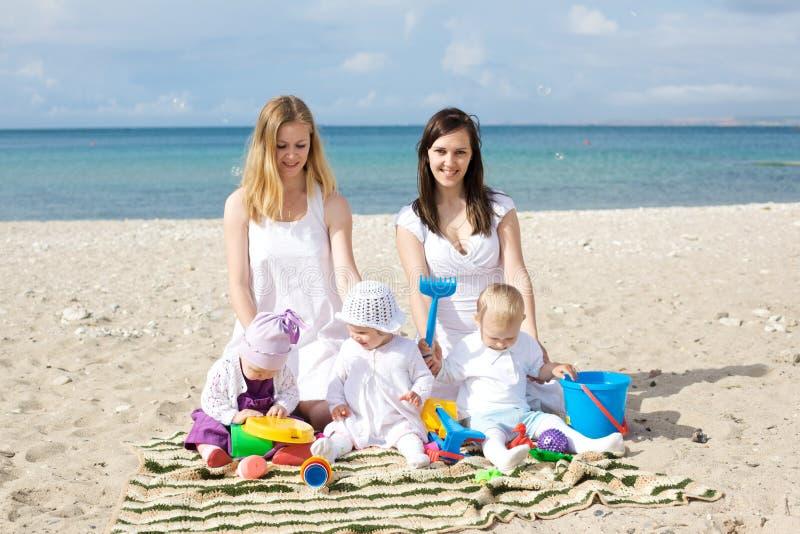 Gelukkige moeders met kinderen bij het strand stock afbeelding