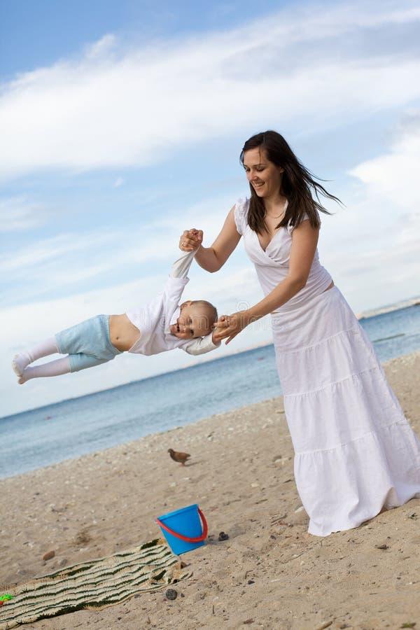 Gelukkige moeders met kinderen bij het strand royalty-vrije stock afbeelding
