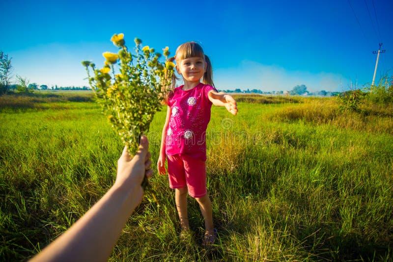 Gelukkige moedersdag! De kinddochter wenst mamma geluk en geeft haar bloemenboeket royalty-vrije stock afbeeldingen