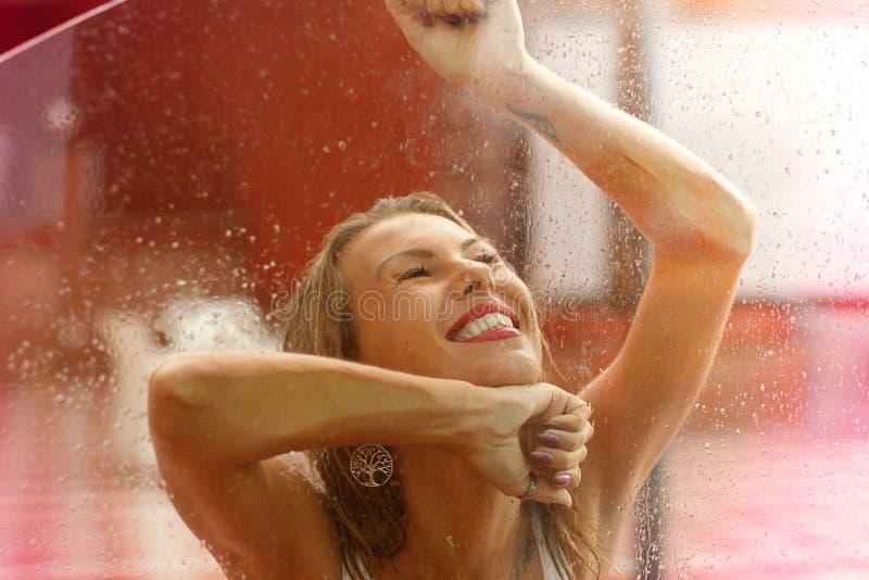 Gelukkige mooie blonde vrouw die onder regen in de herfst lachen stock afbeelding