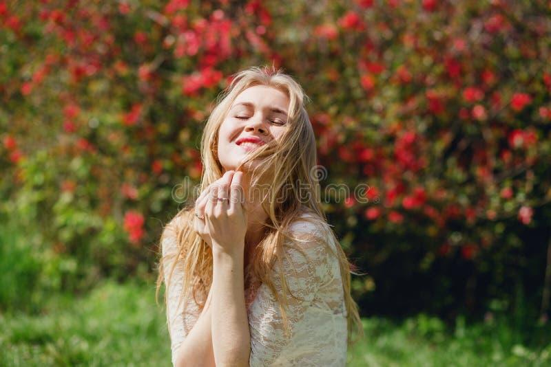 Gelukkige mooie blonde vrouwelijke zitting in bloeiende tuin, vrouw met gesloten ogen die van schoonheid van aard, ontspanning ge royalty-vrije stock afbeeldingen