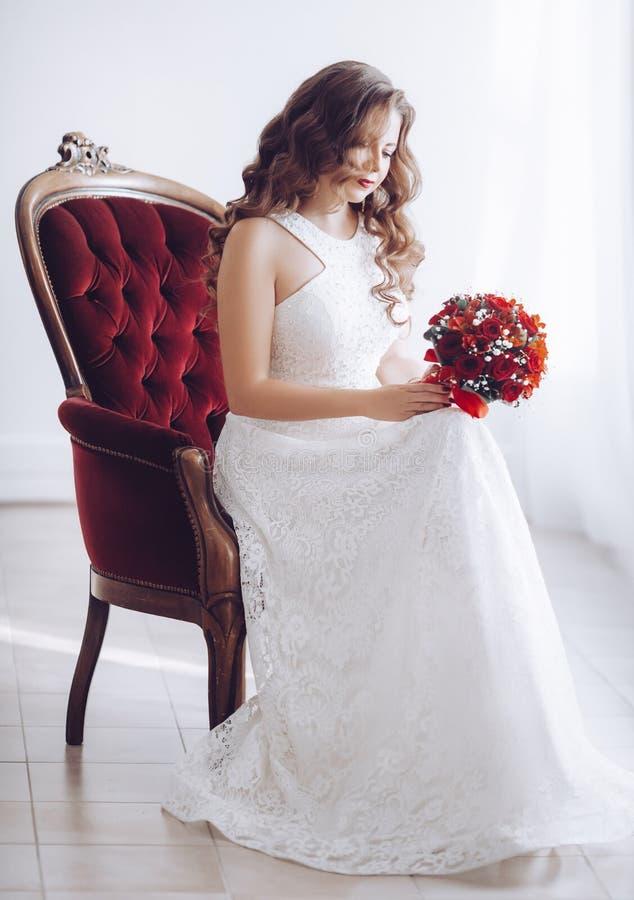 Gelukkige mooie bruid in witte kleding met rode rozen royalty-vrije stock afbeeldingen