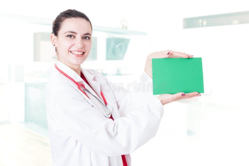 Gelukkige mooie chirurg die leeg document houden stock foto's