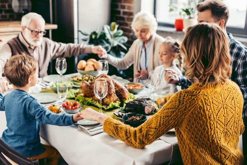 gelukkige mooie familie die vóór vakantiediner bidden stock afbeeldingen