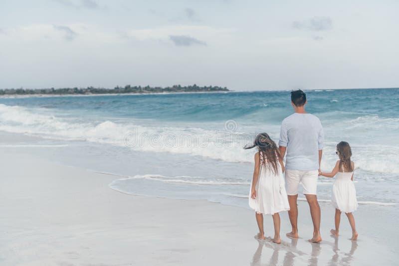 Gelukkige mooie familie van papa en jonge geitjes op wit strand stock foto's