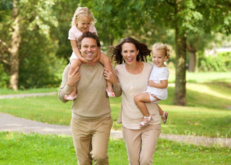 Gelukkige mooie familie van vier die in park lopen royalty-vrije stock afbeeldingen