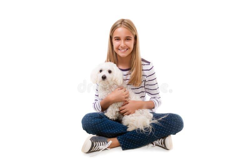 Gelukkige mooie geïsoleerde meisjeszitting op de vloer met Maltese hond op haar knie, stock afbeeldingen
