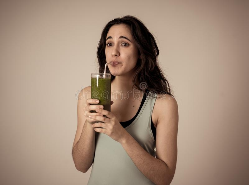 Gelukkige mooie geschikte sportvrouw die en gezonde verse groentedetox glimlachen drinken smoothie stock foto