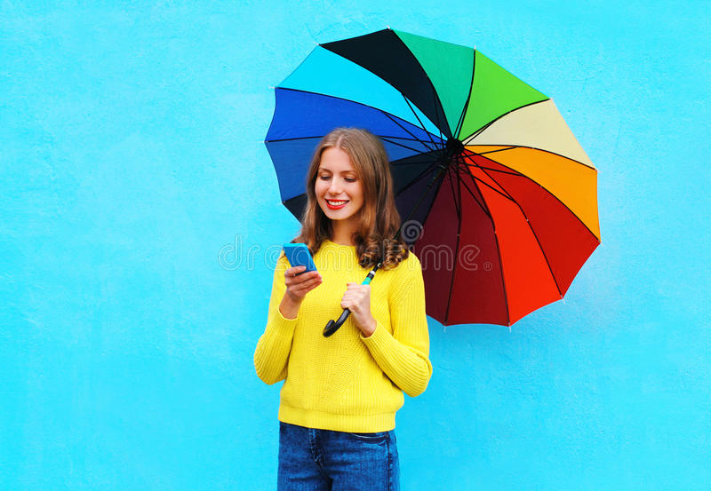 Gelukkige mooie glimlachende jonge vrouw met kleurrijke paraplu die smartphone in de herfstdag over kleurrijke blauwe achtergrond royalty-vrije stock fotografie
