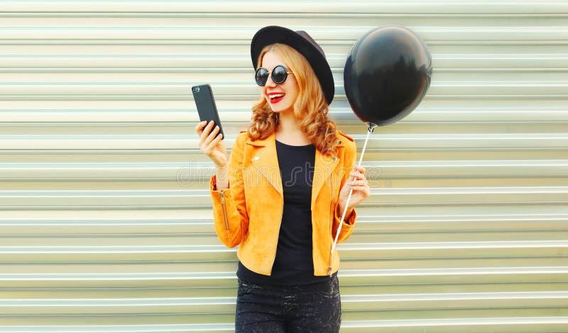 gelukkige mooie glimlachende vrouw die met telefoon de zwarte ballon van de heliumlucht houden royalty-vrije stock afbeelding