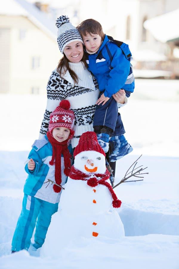 Gelukkige mooie het stichten van een gezinsneeuwman in tuin, de wintertijd, stock afbeeldingen