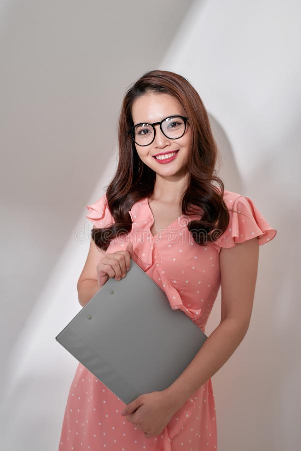 Gelukkige mooie jonge bedrijfsvrouw die en klembord over witte achtergrond bevinden zich houden stock foto