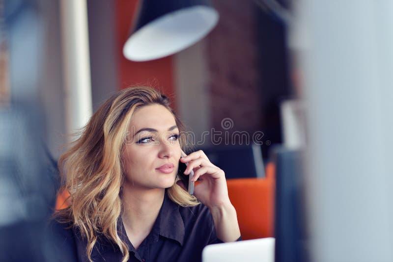 Gelukkige mooie jonge bedrijfsvrouwenzitting en het spreken op celtelefoon in bureau stock afbeelding