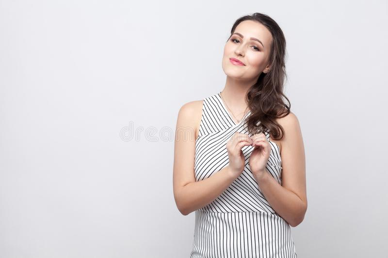 Gelukkige mooie jonge donkerbruine vrouw met make-up en gestreepte kleding die, zich bij camera met glimlach en vriendelijkheid e stock afbeeldingen