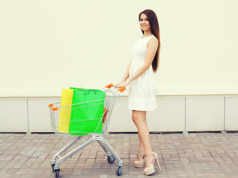 Gelukkige mooie jonge glimlachende vrouw in witte kleding met boodschappenwagentje stock afbeelding