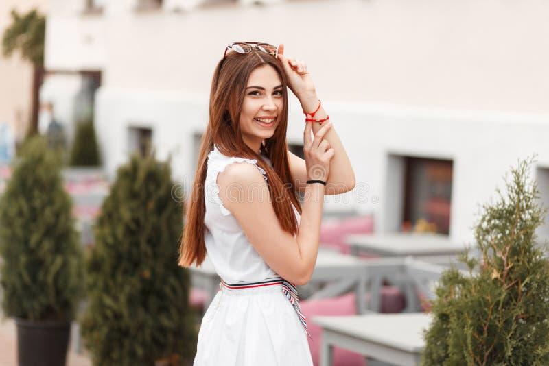 Gelukkige mooie jonge modelvrouw in witte kleding die in openlucht stellen stock afbeelding