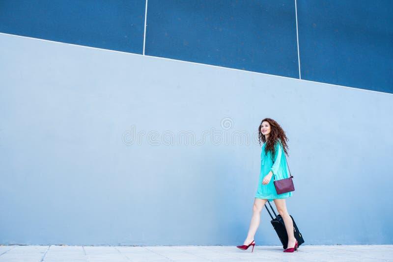 Gelukkige mooie jonge roodharigevrouw met een koffer die door kleurrijk lopen stock afbeelding