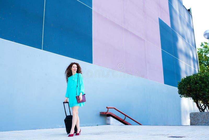 Gelukkige mooie jonge roodharigevrouw met een koffer die door kleurrijk lopen royalty-vrije stock fotografie