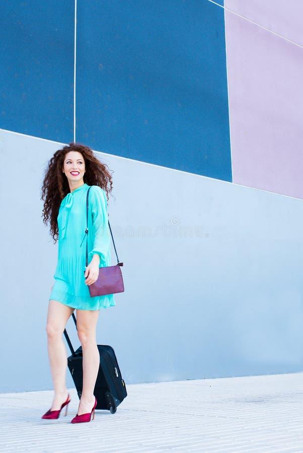Gelukkige mooie jonge roodharigevrouw met een koffer die door a lopen stock afbeeldingen