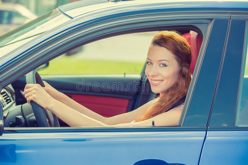 Gelukkige mooie jonge vrouw die haar nieuwe blauwe auto drijven royalty-vrije stock foto's