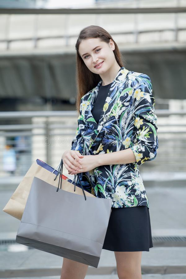 Gelukkige mooie jonge vrouw die met het winkelen zakken op straat in stad genieten van Modieus meisje royalty-vrije stock afbeelding