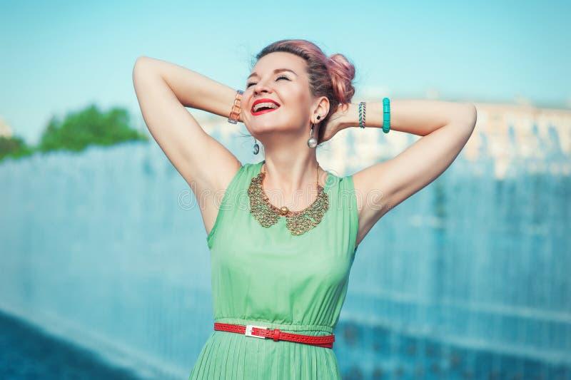 Gelukkige mooie jonge vrouw met steunen in uitstekende kleding stock foto