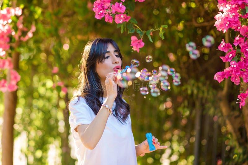 Gelukkige mooie jonge vrouwen blazende zeepbels openlucht royalty-vrije stock afbeelding