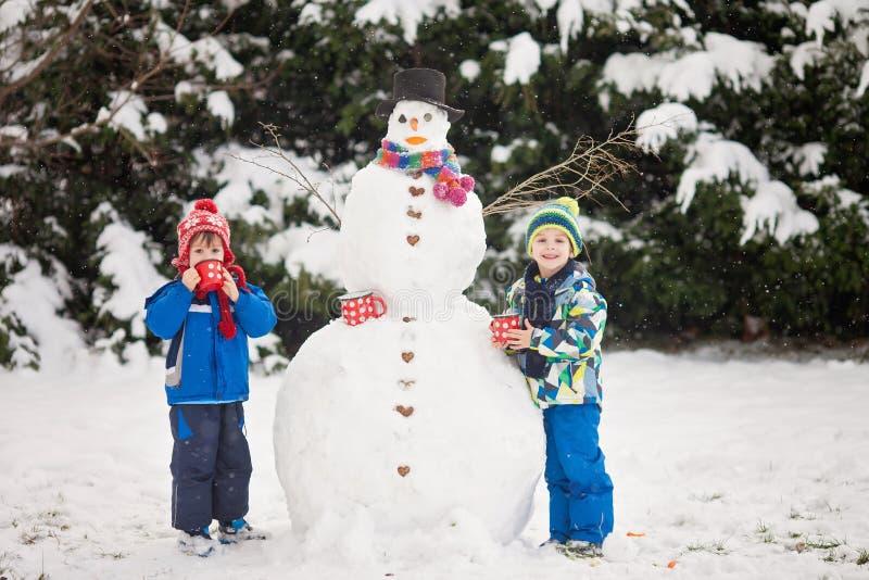 Gelukkige mooie kinderen, broers, bouwsneeuwman in tuin stock afbeeldingen