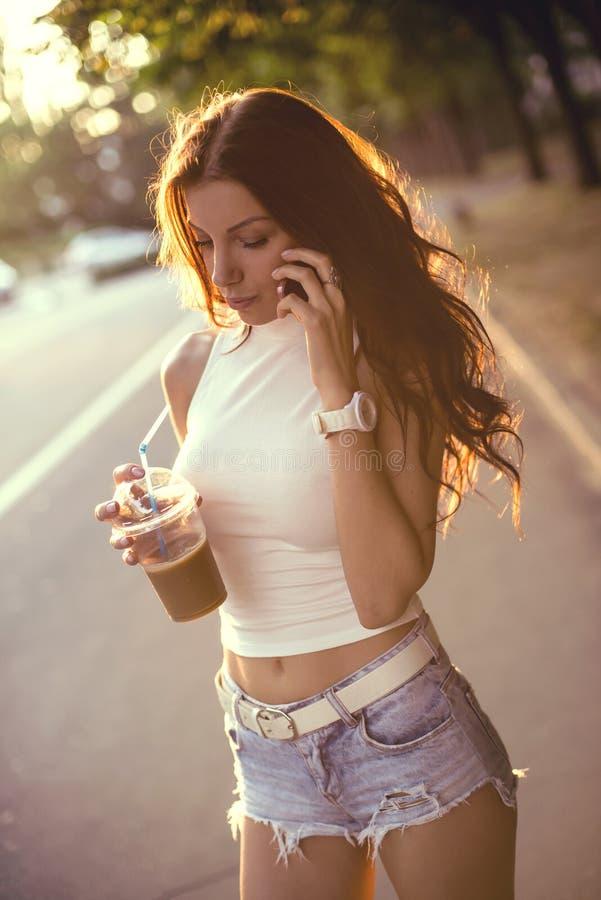 Gelukkige mooie meisje het drinken ijskoffie en het spreken op de telefoon royalty-vrije stock foto