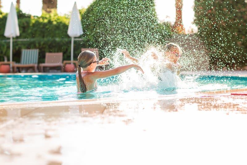 Gelukkige mooie meisjes die pret hebben bij de pool stock foto's