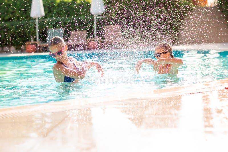 Gelukkige mooie meisjes die pret hebben bij de pool royalty-vrije stock foto's