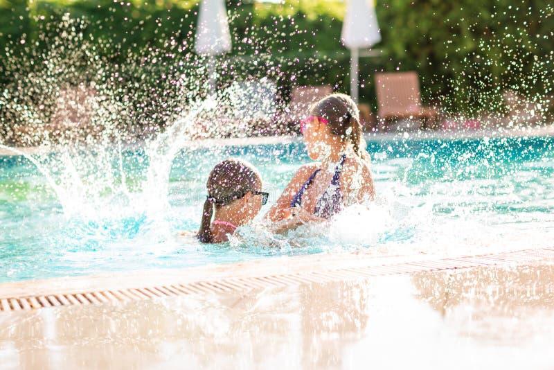 Gelukkige mooie meisjes die pret hebben bij de pool royalty-vrije stock afbeeldingen