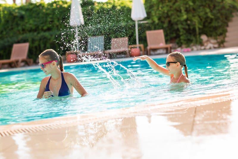 Gelukkige mooie meisjes die pret hebben bij de pool royalty-vrije stock afbeelding