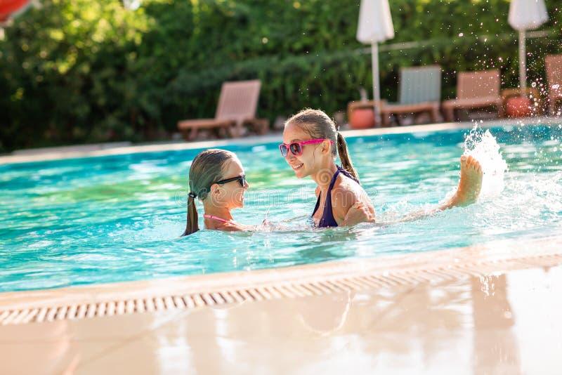 Gelukkige mooie meisjes die pret hebben bij de pool stock afbeeldingen