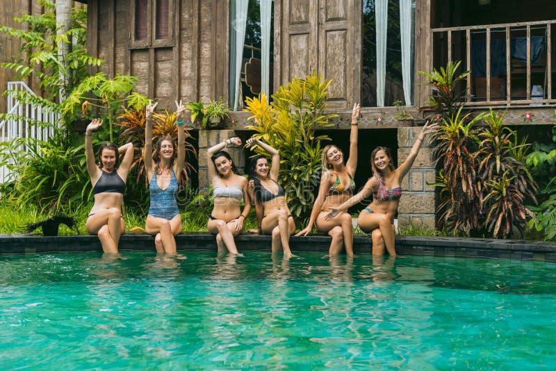 gelukkige mooie meisjes in swimwear zitting bij zwembad en het glimlachen royalty-vrije stock foto