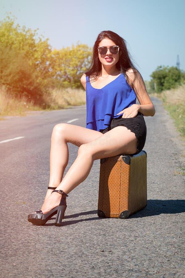 Gelukkige mooie meisjesreiziger met een koffer op de weg, hapering stock afbeeldingen