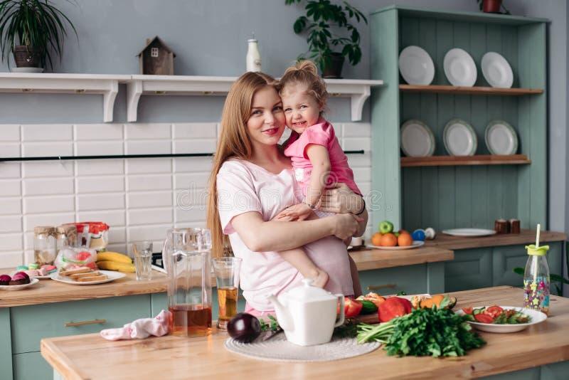 Gelukkige mooie moeder met dochter in ochtendkeuken royalty-vrije stock afbeeldingen