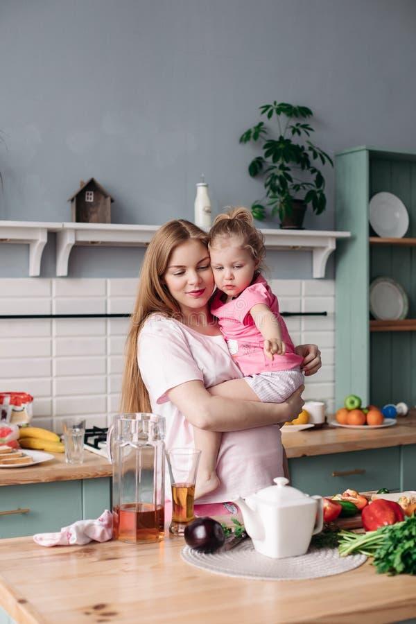 Gelukkige mooie moeder met dochter in ochtendkeuken royalty-vrije stock fotografie