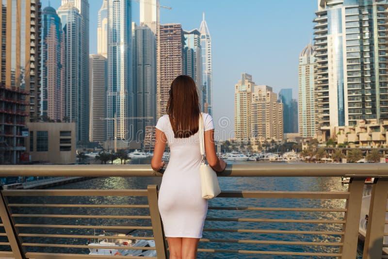 Gelukkige mooie onherkenbare toeristenvrouw die in modieuze de zomer witte kleding in de jachthaven van Doubai in Verenigde Arabi royalty-vrije stock foto's