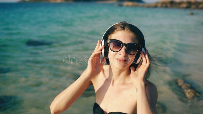 Gelukkige mooie vrouw die aan muziek op draadloze hoofdtelefoons op strand dichtbij overzees luisteren royalty-vrije stock foto's