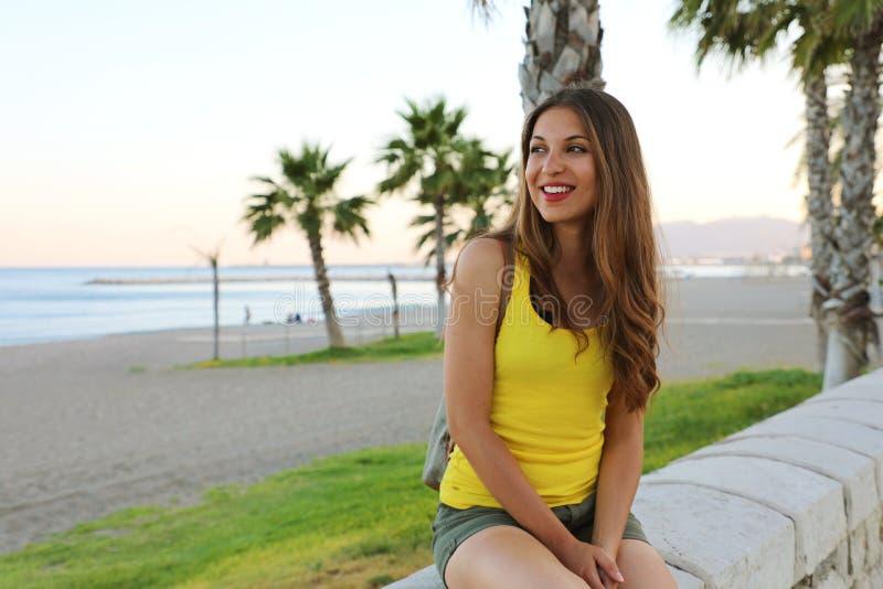 Gelukkige mooie vrouw die en het strand zonsondergang in haar Spaanse vakantie zitten bekijken, Malaga, Spanje royalty-vrije stock afbeelding